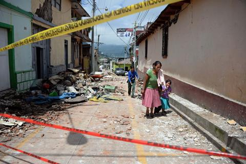 People walk past houses damaged by an earthquake, in San Marcos, 240 km of Guatemala City, on July 7, 2014. A strong 6.9-magnitude earthquake rocked parts of southern Mexico and Guatemala on Monday, killing at least two people and injuring more than 40 others. The US Geological Survey said the quake -- initially measured at a magnitude of 7.1 -- struck the Pacific coast of Mexico's Chiapas state at about 1124 GMT at a depth of 60 km. The epicenter was located just two km from the Mexican town of Puerto Madero, and 200 km from Guatemala City.