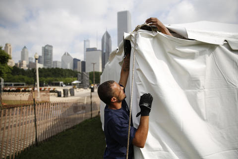 Isreal Medina sets up one of the tents near the Petrillo Music Shell for the Taste of Chicago.