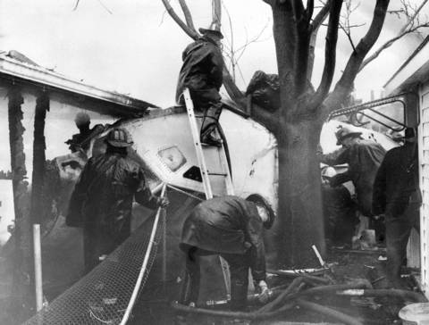 Firemen work to free a stewardess whose screams they can hear from the cockpit of United Airlines Flight 553 that crashed into a row of bungalows while approaching Midway Airport in Chicago.