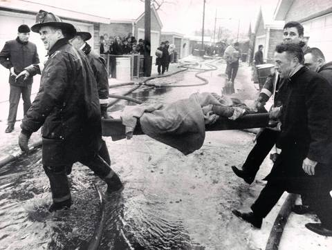 "Surviving stewardess Marguerite McCausland is carried from the wreckage of the United Airlines jet crash in Chicago on Dec. 8, 1972. She was rescued from the front end of the aircraft. Her rescuer, John ""Duke"" O'Malley, a Chicago firefighter, who's face is visible in the top right part of the photograph, helps to carry her to safety."