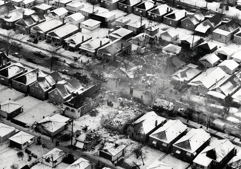 A photograph taken the day after the crash of United Airlines Flight 553 shows where the jetliner crashed into a row of bungalows on West 70th Place while approaching Midway Airport. 43 of the 61 persons aboard, and two in a home, were killed.