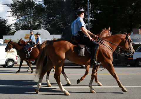 Mounted police officers pass each other at the Taste of Chicago grounds.