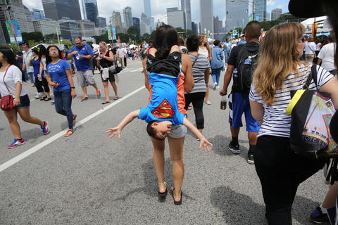 Billy Brown hangs from his sister Sam's shoulder during the opening day at Taste of Chicago.
