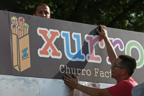 Carlos Covarrubias, left, drills as Eddie Olmos holds a sign in place in preparation for the Taste of Chicago.