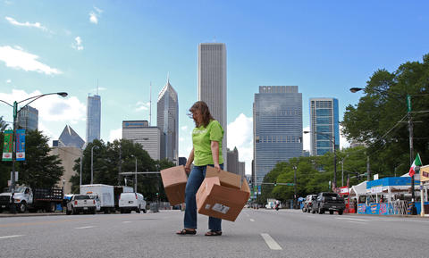 A worker carries boxes to a booth at the Taste of Chicago grounds on South Columbus Drive.