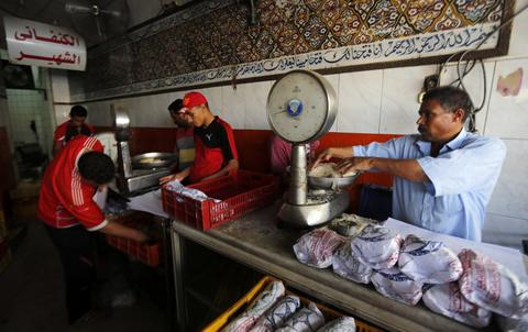 Employees wrap traditional sweets in paper for customers at the Arafah Al Kanafani, a shop selling traditional sweets, in old Cairo July 9, 2014. Arafah, which started operations in 1870, is one of the oldest pastry shops in Egypt that sells traditional desserts such as kunafa and qatayef during the holy fasting month of Ramadan, according to the owner Haj Mahmoud Arafah, who is from the Arafah family that founded the shop.