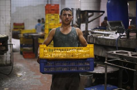 Mohamed, 16, carries trays of dough to make kunafa, in the factory of Arafah Al Kanafani, a shop selling traditional sweets, in old Cairo July 9, 2014. Arafah, which started operations in 1870, is one of the oldest pastry shops in Egypt that sells traditional desserts such as kunafa and qatayef during the holy fasting month of Ramadan, according to the owner Haj Mahmoud Arafah, who is from the Arafah family that founded the shop.