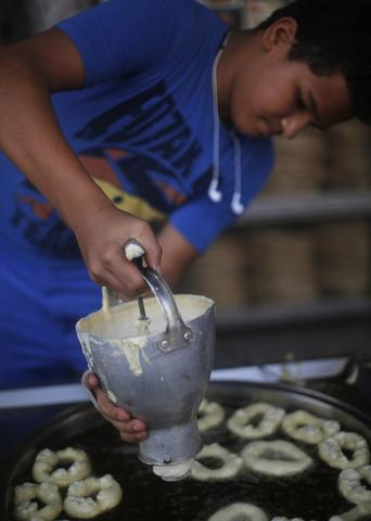 "A worker makes ""Lukmet Arafah"" sweets at Arafah Al Kanafani, a shop selling traditional sweets, in old Cairo July 9, 2014. Arafah, which started operations in 1870, is one of the oldest pastry shops in Egypt that sells traditional desserts such as kunafa and qatayef during the holy fasting month of Ramadan, according to the owner Haj Mahmoud Arafah, who is from the Arafah family that founded the shop."