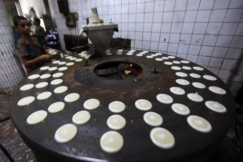 "Eslam, 11, works on qatayef at the factory of Arafah Al Kanafani, a pastry shop selling traditional sweets, in old Cairo July 9, 2014. Arafah, which started operations in 1870, is one of the oldest pastry shops in Egypt that sells traditional desserts such as ""Kunafa"" and ""Qatayef"" during the holy fasting month of Ramadan, according to the owner Haj Mahmoud Arafah, who is from the Arafah family that founded the shop."