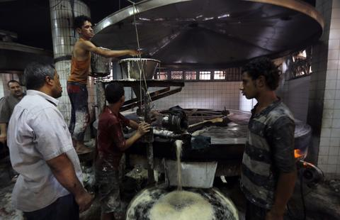 Employees work on dough for kunafa at a machine in the factory of Arafah Al Kanafani, a shop selling traditional sweets, in old Cairo July 9, 2014. Arafah, which started operations in 1870, is one of the oldest pastry shops in Egypt that sells traditional desserts such as kunafa and qatayef during the holy fasting month of Ramadan, according to the owner Haj Mahmoud Arafah, who is from the Arafah family that founded the shop.