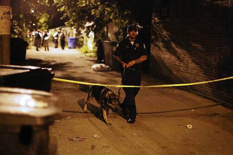 An officer and his dog cross under police tape at the scene where officers exchanged gunfire with a man near the intersection of West 64th Street and South Campbell Avenue in Chicago.
