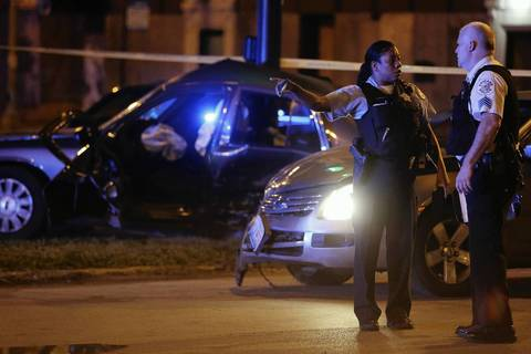 Police officers talk near the scene where an unmarked police car was involved in an collision with a grey sedan just before 11 p.m. on Wednesday at the intersection of East Garfield Boulevard and South Indiana Avenue in Chicago.