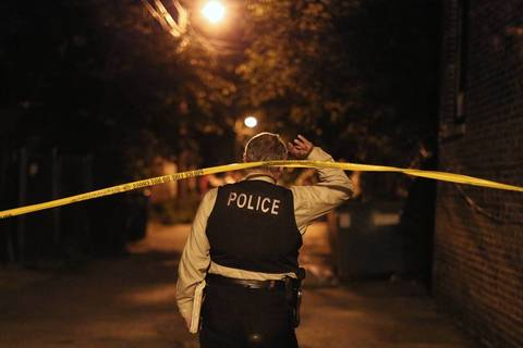 A detective crosses under police tape at the scene where officers exchanged gunfire with a man.