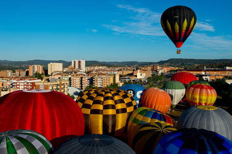A Hot air balloons flies over Igualada during an early flight as part of the European Balloon Festival on July 10, 2014 in Igualada, Spain. The early morning flight of over 30 balloons was shorter than expected due to windy weather. This flight is organised as a curtain raiser for the four-day European Balloon Festival. Now is the 18th year of the most important hot air Balloon event in Spain and one of the biggest in Europe.