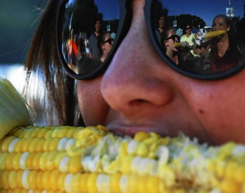 Alyssa Fleischman eats an ear of corn as friends Jessie Fisher and Emily Will (right), all 19, are shown in the reflection of Fleischman's sunglasses at the Taste of Chicago.