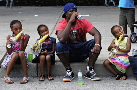 Rayshon Winston drinks fruit juice as India White, 10, (from left) Raven Winston, 5, and Riley Winston, 4, bite into ears of corn at the Taste of Chicago.
