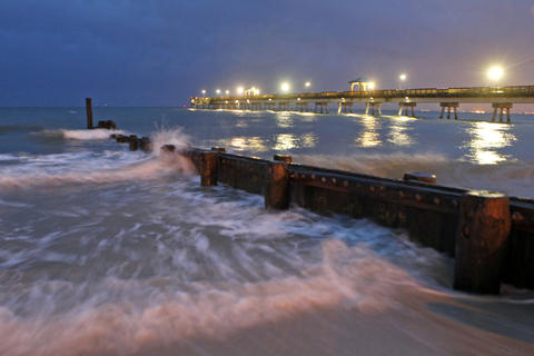 Waves crash into the shore of Buckroe Beach as the sun begins to rise Friday morning.