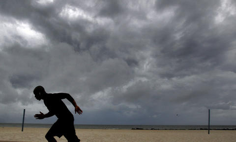 Kejuan Torrence runs near the shore of Buckroe Beach as Hurricane Arthur passes by Hampton Roads on Friday morning.
