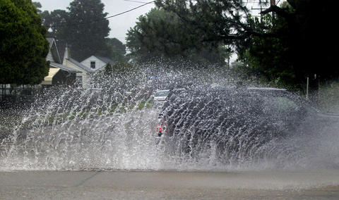 A truck drives through a puddle along Mercury Boulevard after Hurricane Arthur brought heavy rains to the area on Friday morning.