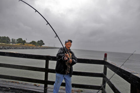 "Clarence Futrell fishes off the pier of Fort Monroe as rain and wind fill the air Friday morning. ""If the fish weren't biting, I wouldn't be out here,"" said Futrell."