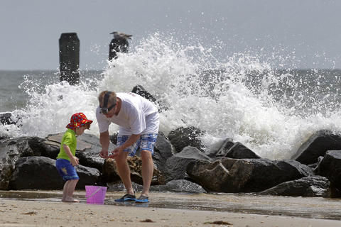 Greg McCauley inspects rocks with his two-year-old Gabriel as waves crash into rocks on the shore of Buckroe Beach after Hurricane Arthur passed on Friday morning.