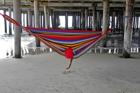 Erica Carcamo, 4, plays in the sand while laying in a hammock as waves wash ashore underneath the pier of Buckroe Beach after Hurricane Arthur passed on Friday morning.