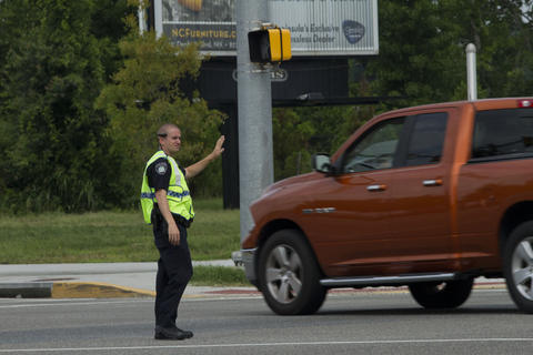 Newport News police direct cars by a downed traffic light on the corner of Jefferson Avenue and Mercury Boulevard on Friday.