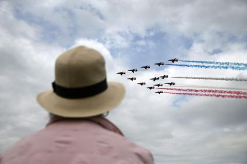 An aviation enthusiast watches The Royal Air Force aerobatic team, the Red Arrows, perform during The Royal International Air Tattoo at the RAF in Fairford July 11, 2014.