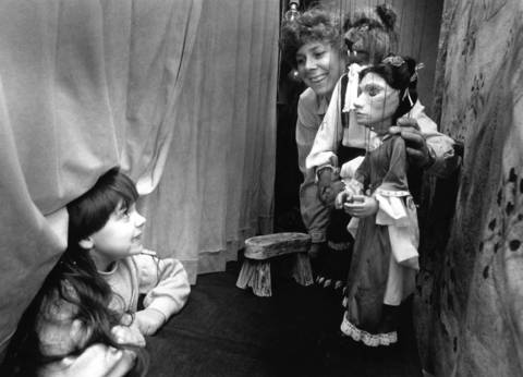 Feb. 12, 1990: Megan Rosengren, 5, sneaks behind the curtain to chat with puppeteer Linda Roberts during a puppet show at Bolingbrook's Fountaindale Public Library.