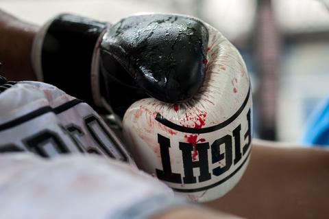 Detail of a bloody boxing glove as an inmate rests during a Muay Thai fight at Klong Pai prison on July 12, 2014 in Nakhon Ratchasima, Thailand. Prison Fight is an sport event which takes place in different prisons in Thailand and involves inmates fighting against foreign fighters looking for their rehabilitation, to promote the sport and good health among prisoners and to help them with better social adaptation for the future. Thailand has a strong tradition in fight sports such as Muay Thai and boxing, and inmates can reduce their jail sentence fighting in this event organized between World Prison Fight Association (WPFA) with the assistance of the Department Of Corrections.