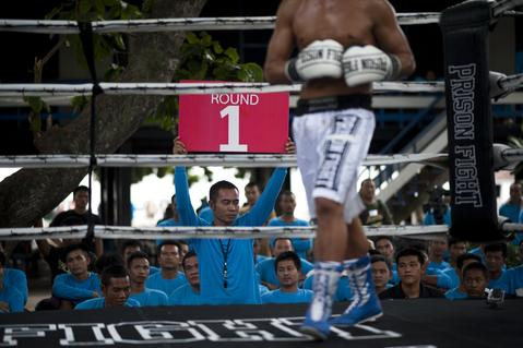 An inmate shows a 'Round 1' banner during a boxing fight at Klong Pai prison on July 12, 2014 in Nakhon Ratchasima, Thailand. Prison Fight is an sport event which takes place in different prisons in Thailand and involves inmates fighting against foreign fighters looking for their rehabilitation, to promote the sport and good health among prisoners and to help them with better social adaptation for the future. Thailand has a strong tradition in fight sports such as Muay Thai and boxing, and inmates can reduce their jail sentence fighting in this event organized between World Prison Fight Association (WPFA) with the assistance of the Department Of Corrections.