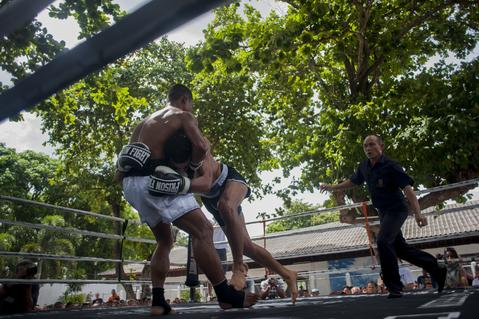 A foreign fighter pushes an inmate fighter during a Muay Thai fight at Klong Pai prison on July 12, 2014 in Nakhon Ratchasima, Thailand. Prison Fight is an sport event which takes place in different prisons in Thailand and involves inmates fighting against foreign fighters looking for their rehabilitation, to promote the sport and good health among prisoners and to help them with better social adaptation for the future. Thailand has a strong tradition in fight sports such as Muay Thai and boxing, and inmates can reduce their jail sentence fighting in this event organized between World Prison Fight Association (WPFA) with the assistance of the Department Of Corrections.