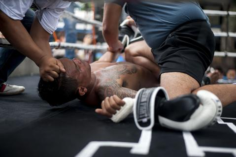 An inmate is helped after he falls to the floor during a Muay Thai fight at Klong Pai prison on July 12, 2014 in Nakhon Ratchasima, Thailand. Prison Fight is an sport event which takes place in different prisons in Thailand and involves inmates fighting against foreign fighters looking for their rehabilitation, to promote the sport and good health among prisoners and to help them with better social adaptation for the future. Thailand has a strong tradition in fight sports such as Muay Thai and boxing, and inmates can reduce their jail sentence fighting in this event organized between World Prison Fight Association (WPFA) with the assistance of the Department Of Corrections.