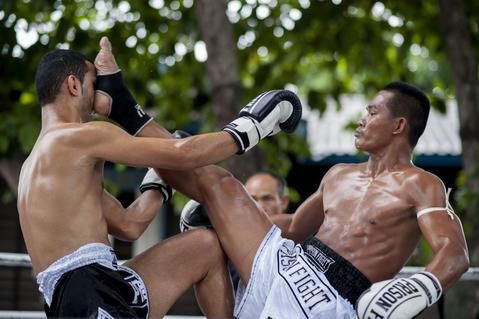 An inmate kicks a foreigner fighter during a Muay Thai fight at Klong Pai prison on July 12, 2014 in Nakhon Ratchasima, Thailand. Prison Fight is an sport event which takes place in different prisons in Thailand and involves inmates fighting against foreign fighters looking for their rehabilitation, to promote the sport and good health among prisoners and to help them with better social adaptation for the future. Thailand has a strong tradition in fight sports such as Muay Thai and boxing, and inmates can reduce their jail sentence fighting in this event organized between World Prison Fight Association (WPFA) with the assistance of the Department Of Corrections.