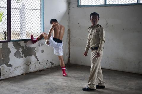 An inmate prepares himself before his fight as a prison officer stands guard at Klong Pai prison on July 12, 2014 in Nakhon Ratchasima, Thailand. Prison Fight is an sport event which takes place in different prisons in Thailand and involves inmates fighting against foreign fighters looking for their rehabilitation, to promote the sport and good health among prisoners and to help them with better social adaptation for the future. Thailand has a strong tradition in fight sports such as Muay Thai and boxing, and inmates can reduce their jail sentence fighting in this event organized between World Prison Fight Association (WPFA) with the assistance of the Department Of Corrections.