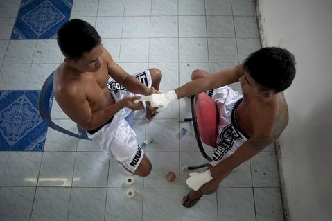 Two inmate fighters prepare themsleves for a fight at Klong Pai prison on July 12, 2014 in Nakhon Ratchasima, Thailand. Prison Fight is an sport event which takes place in different prisons in Thailand and involves inmates fighting against foreign fighters looking for their rehabilitation, to promote the sport and good health among prisoners and to help them with better social adaptation for the future. Thailand has a strong tradition in fight sports such as Muay Thai and boxing, and inmates can reduce their jail sentence fighting in this event organized between World Prison Fight Association (WPFA) with the assistance of the Department Of Corrections.