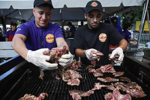 Greg Martinez (left) and Jon Rivera prepare carne asada on a grill at the Taste of Chicago.