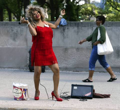 "Street performer and Tina Turner impersonator Dorothy Roberson works her magic singing ""What's Love Got to Do With It"" on Jackson Boulevard near the entrance to Taste of Chicago."