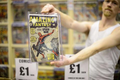 A stallholder holds up a copy of the first comicbook to feature Spiderman, priced at 5,000 GBP (8,500 USD), at the London Film and Comic Con 2014 in Earls Court, west London, on July 13, 2014. The event lets enthusiasts purchase rare items before getting the chance to meet film stars, TV actors, wrestlers and other personalities in the signing and photo zones. AFP PHOTO / LEON NEALLEON NEAL/AFP/Getty Images ORG XMIT: