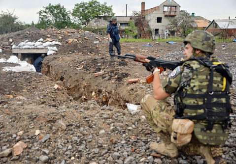 A Ukrainian serviceman patrols as deminers neutralize mines and other explosives in the village of Semenovka, near the eastern Ukrainian city of Slavyansk in the Donetsk region on July 14.