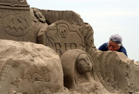 Sand artists build their sculptures at Yasashigaura beach in Asahi, Chiba prefecture on July 13, 2014.