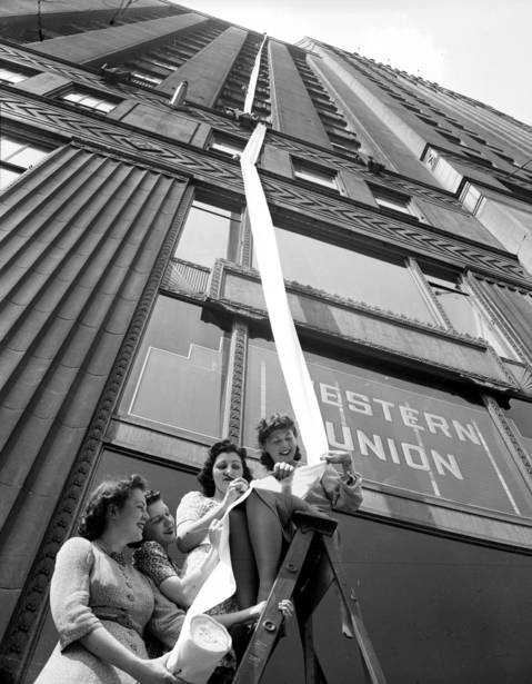 Juliet Foley, from left, Karoyla Richter, Dorothy Gaskin, and Georgina Lov Flagler, hold onto a letter from Merchandise Mart employees to soldiers in 1941. The letter was 240 feet long.