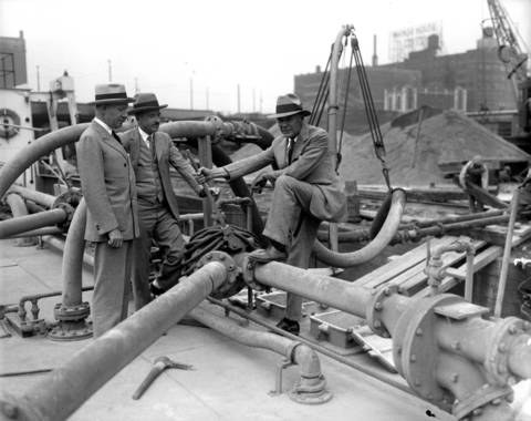 George Griffiths, left, one of the builders of the Merchandise Mart, Claude A. Welles, general manager of the Merchandise Mart, and C. C. West, atop the building during construction in 1928.