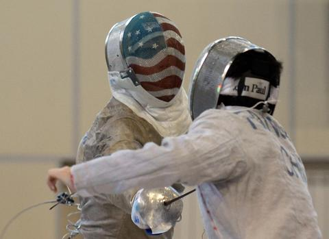 Benjamin Igoe of the United States (L) competes against Xin Fang of China during the men's sabre qualification competition at the World Fencing Championships in Kazan, on July 15, 2014.