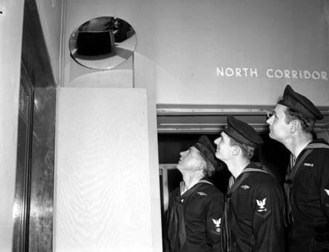 R. G. Becker, R. A. Martin, and H. L. Kluska, look at a mirror on the second floor that shows the elevator starter on the first floor if a crowd is waiting on the first floor on April 15, 1954. The device was a periscope system for the elevators.