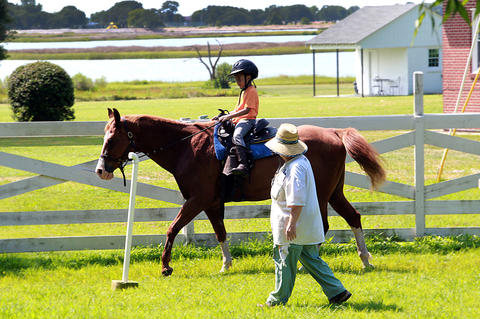 Susie Mirick, a horsewoman and retired dean from The College of William and Mary, walks along in the ring with Alexis Poindexter, who is taking part in the equestrian summer day camp at the Hampton University stables.