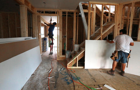 Victor Tapia, on drywall stilts, left, and Jose Ramirez are installing drywall at a new construction house at Buckroe Beach.