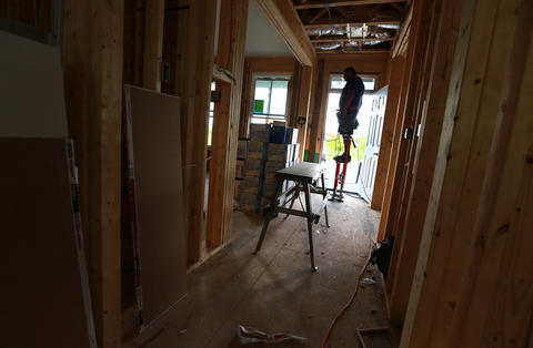 Victor Tapia, on drywall stilts, is working steady at a new construction house at Buckroe Beach