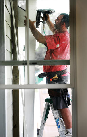 Viewed through a window, Mike Sandoval is attaching trim on a new construction house at Buckroe Beach.