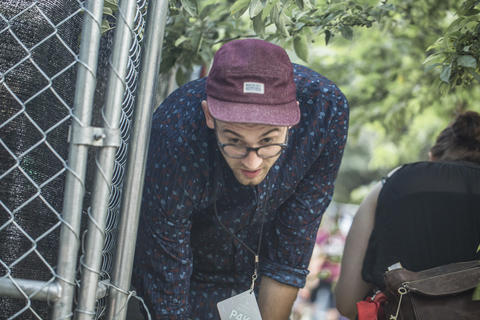 A Pitchfork attendee is forced to duck under a tree that is placed right in front of the entrance of the VIP section.